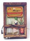 In einer alten Holzkiste für Imker ist eine Blechdose mit der Aufschrift: Gehirn-Direkt-Nahrung montiert. Darunter sind 3 blinkende Glasscheiben.